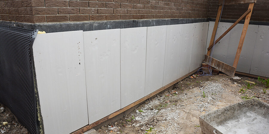 foundation and basement thermal polystyrene insulation: rigid eps foam boards are installed before applying waterproofing membrane to insulate the exterior foundation wall of a new house.